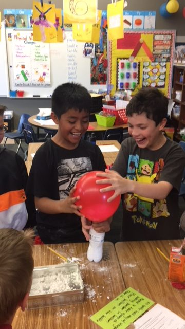 two boys use a red balloon to pour flower into a water bottle