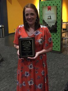 teacher in red floral dress holding award for science teacher of the year