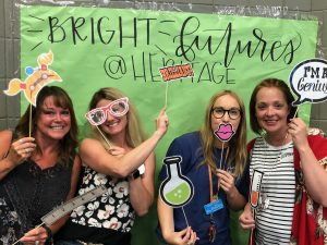teachers using science photobooth props in front of a green sign