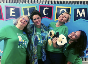 teachers wearing green shirts posing in front of a welcome sign