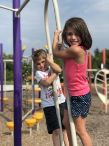 girl in pink shirt and blue shorts standing on playground equipment with boy wearing white shirt with writing