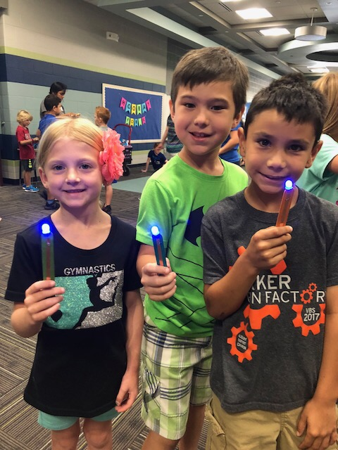 three students holding up their popsicle circuits with LED Lights