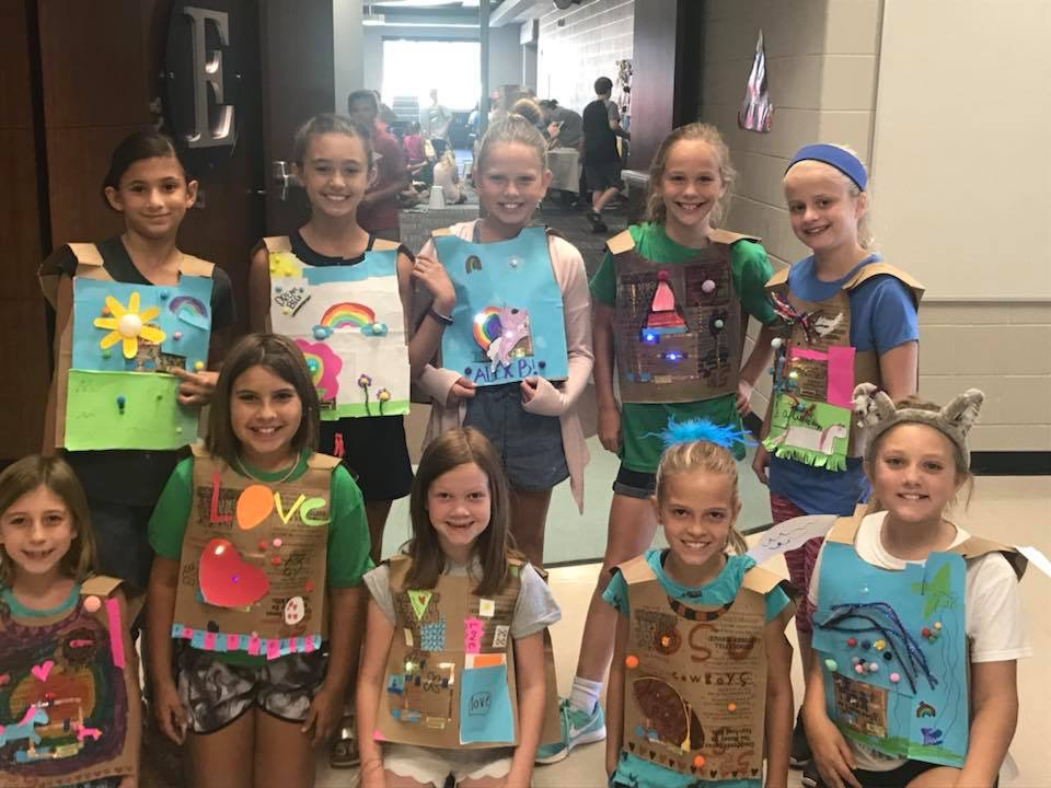 group of girls wearing decorated vests made of paper bags