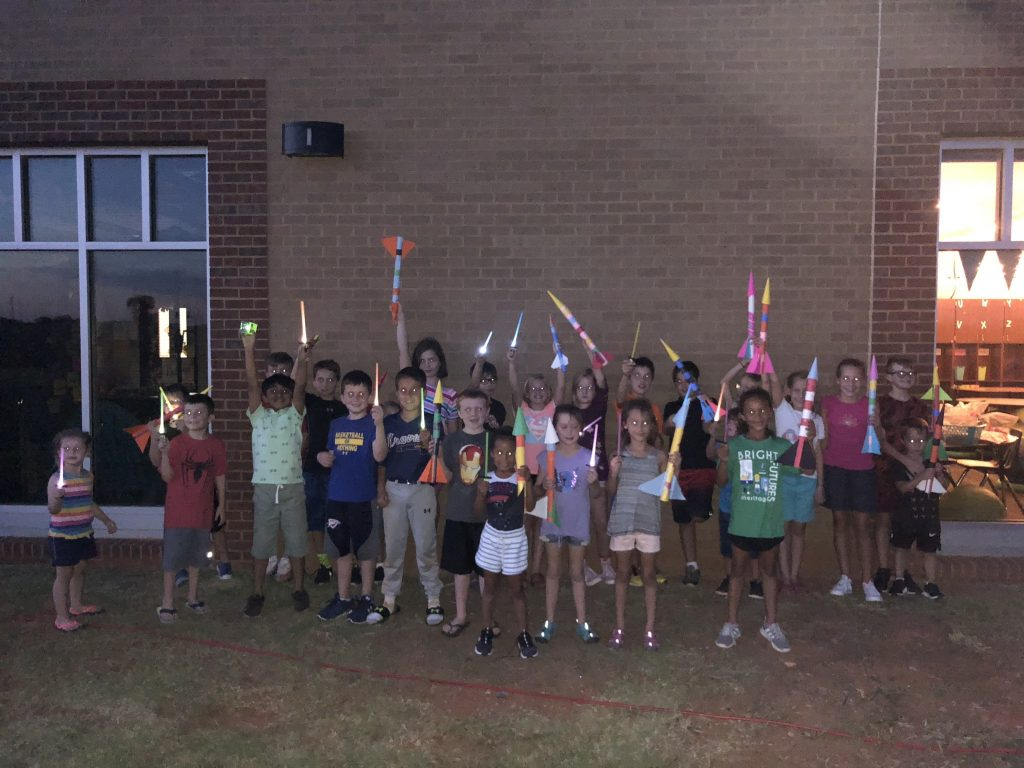 Heritage families and students displaying their products of Light Up the Night!