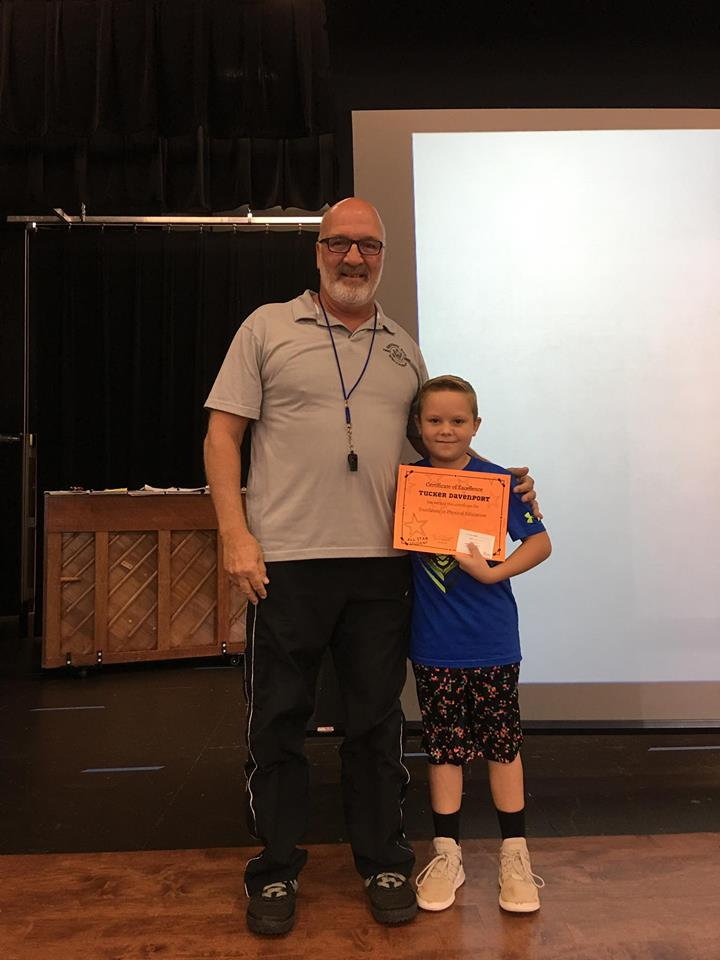 male student accepting award from PE coach