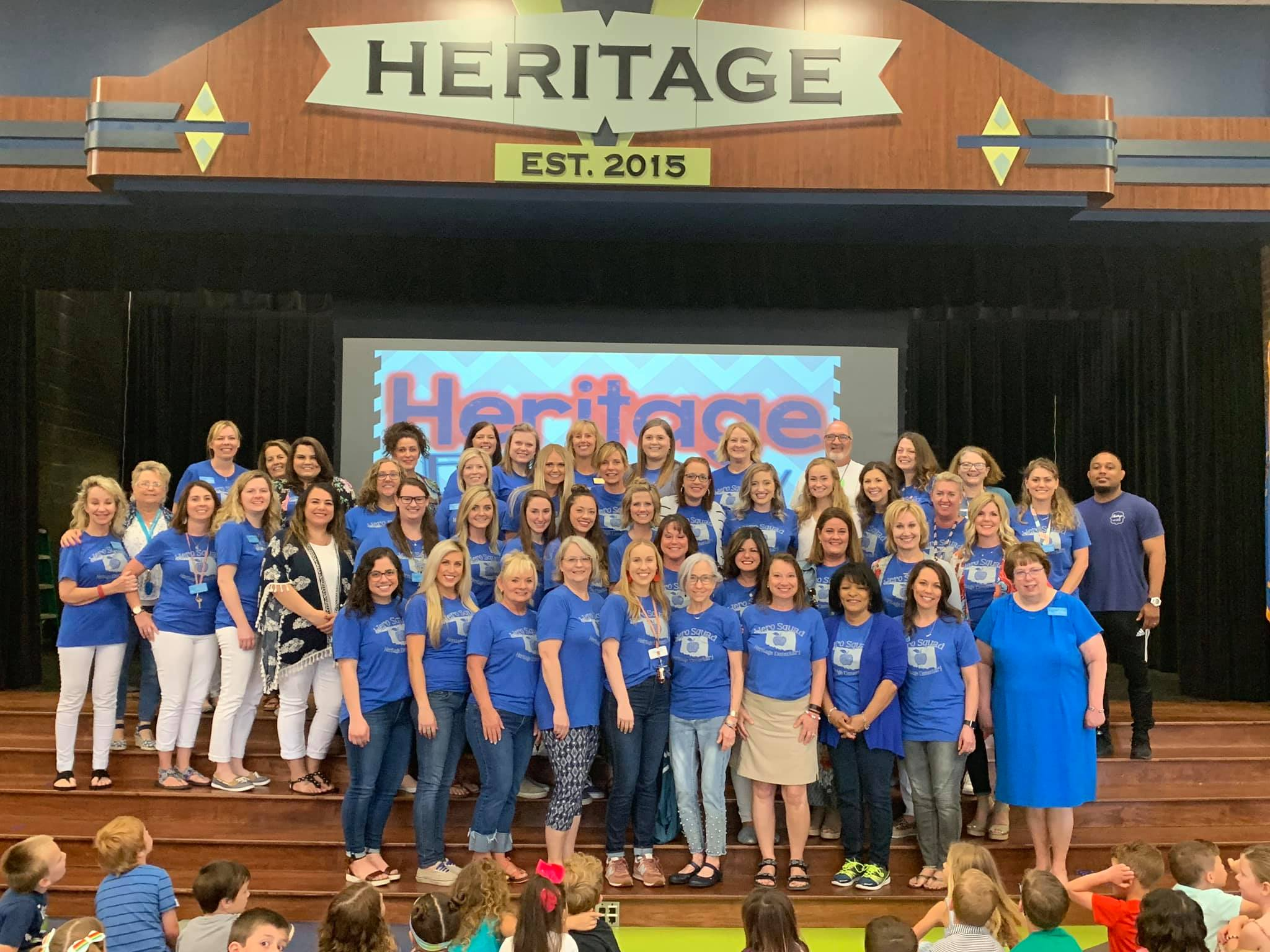 Teachers standing on stage wearing blue shirts